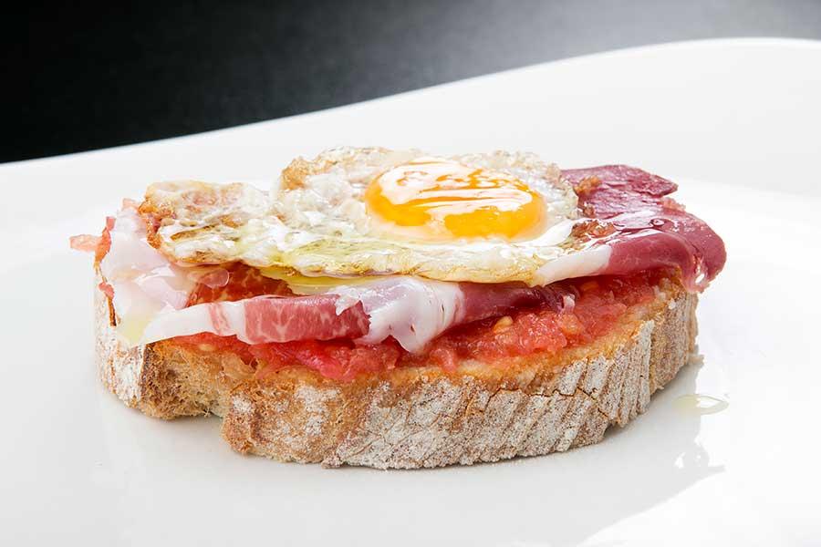 Pan tumaca con jamón y huevo de codorniz